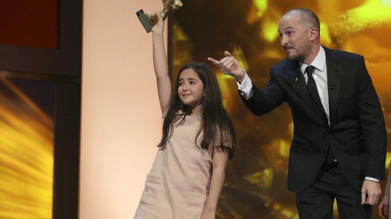 """Hana Saeidi, nièce de Jafar Panahi absent à la cérémonie, brandit l'Ours d'or remporté par son oncle pour le film """"Taxi""""."""